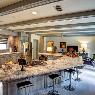マイアミの大きいエクレクティックスタイルのおしゃれなキッチン (アンダーカウンターシンク、レイズドパネル扉のキャビネット、グレーのキャビネット、大理石カウンター、グレーのキッチンパネル、ボーダータイルのキッチンパネル、シルバーの調理設備の、磁器タイルの床) の写真