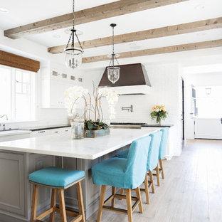 Ispirazione per una grande cucina stile marinaro con lavello stile country, ante in stile shaker, ante bianche, top in marmo, paraspruzzi bianco, elettrodomestici in acciaio inossidabile e parquet chiaro