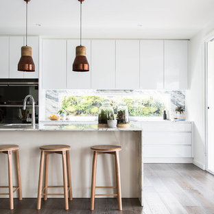 Design ideas for a scandinavian galley kitchen in Melbourne with flat-panel cabinets, white cabinets, window splashback, dark hardwood floors, with island, brown floor, marble benchtops, black appliances and white benchtop.