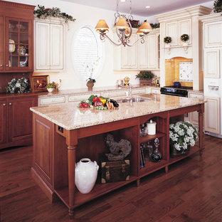 Создайте стильный интерьер: большая отдельная, угловая кухня в викторианском стиле с столешницей из гранита, врезной раковиной, фасадами с выступающей филенкой, фасадами цвета светлого дерева, желтым фартуком, фартуком из керамогранитной плитки, темным паркетным полом, островом, коричневым полом и коричневой столешницей - последний тренд
