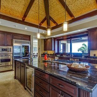 Large tropical u-shaped open plan kitchen in Hawaii with an undermount sink, raised-panel cabinets, brown cabinets, granite benchtops, black splashback, stone slab splashback, stainless steel appliances, travertine floors and with island.
