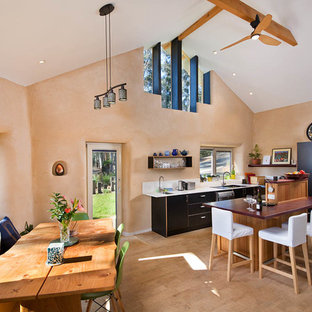 Southwestern eat-in kitchen remodeling - Eat-in kitchen - southwestern l-shaped beige floor eat-in kitchen idea in Sydney with a double-bowl sink, flat-panel cabinets, black cabinets, stainless steel appliances, an island and brown countertops