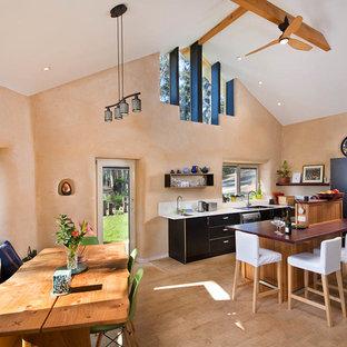 シドニーのサンタフェスタイルのおしゃれなキッチン (ダブルシンク、フラットパネル扉のキャビネット、黒いキャビネット、シルバーの調理設備、ベージュの床、茶色いキッチンカウンター) の写真