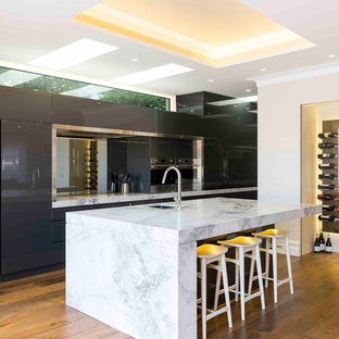 Design ideas for a contemporary kitchen in Sydney with an undermount sink, flat-panel cabinets, grey cabinets, mirror splashback, stainless steel appliances, medium hardwood floors, with island and white benchtop.