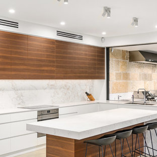 Design ideas for a contemporary l-shaped kitchen in Sydney with a double-bowl sink, flat-panel cabinets, medium wood cabinets, white splashback, stone slab splashback, stainless steel appliances, with island, beige floor and white benchtop.