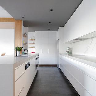 Ejemplo de cocina actual con fregadero bajoencimera, armarios con paneles lisos, puertas de armario blancas, salpicadero blanco, salpicadero de losas de piedra, suelo gris y encimeras grises