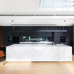 Inspiration for a contemporary eat-in kitchen in Melbourne with a double-bowl sink, flat-panel cabinets, black cabinets, mirror splashback, black appliances, light hardwood floors, with island and white benchtop.