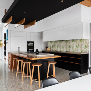 This is an example of a contemporary open plan kitchen in Canberra - Queanbeyan with flat-panel cabinets, white cabinets, multi-coloured splashback, black appliances, with island, multi-coloured floor and green benchtop.