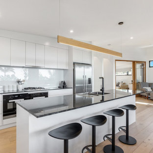 Contemporary open plan kitchen in Sydney with a double-bowl sink, flat-panel cabinets, white cabinets, white splashback, glass sheet splashback, stainless steel appliances, light hardwood floors, with island and black benchtop.