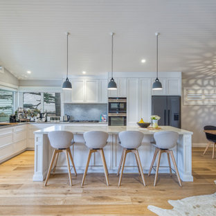 Design ideas for a large beach style l-shaped kitchen in Sydney with a drop-in sink, shaker cabinets, white cabinets, grey splashback, stainless steel appliances, light hardwood floors, with island, beige floor and white benchtop.