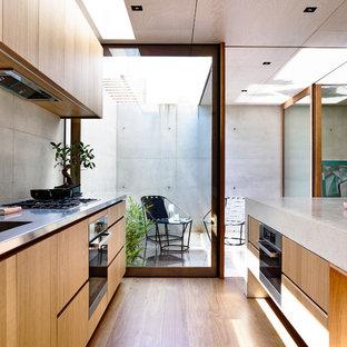 メルボルンの小さいモダンスタイルのおしゃれなキッチン (ダブルシンク、中間色木目調キャビネット、コンクリートカウンター、グレーのキッチンパネル、無垢フローリング、シルバーの調理設備の) の写真
