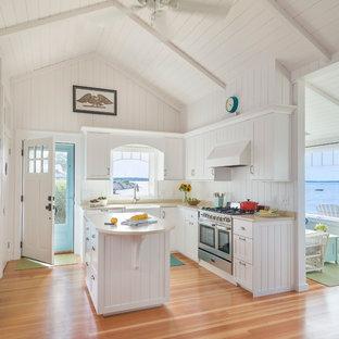 Foto di una cucina ad U stile marino con lavello stile country, ante bianche, elettrodomestici in acciaio inossidabile, pavimento in legno massello medio e isola