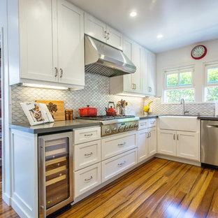 Foto på ett mellanstort vintage kök, med en rustik diskho, skåp i shakerstil, vita skåp, bänkskiva i kvarts, rostfria vitvaror, bambugolv, vitt stänkskydd, stänkskydd i porslinskakel och en halv köksö