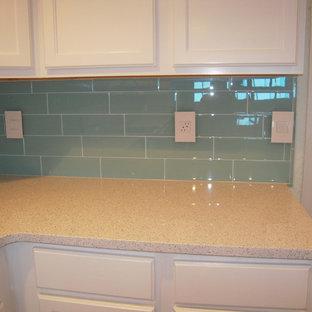 Immagine di una cucina stile marinaro di medie dimensioni con lavello a doppia vasca, ante in stile shaker, ante bianche, top in quarzo composito, paraspruzzi blu, paraspruzzi con piastrelle di vetro, elettrodomestici bianchi, pavimento in gres porcellanato e penisola