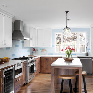 This is an example of a mid-sized transitional l-shaped open plan kitchen with a farmhouse sink, recessed-panel cabinets, quartz benchtops, blue splashback, glass tile splashback, stainless steel appliances, medium hardwood floors, with island, yellow floor, white benchtop and medium wood cabinets.