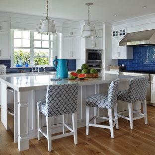 Diseño de cocina marinera, de tamaño medio, con salpicadero azul, electrodomésticos de acero inoxidable, suelo de madera en tonos medios, puertas de armario blancas, armarios estilo shaker, salpicadero de azulejos tipo metro y una isla