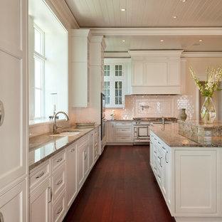 マイアミのトロピカルスタイルのおしゃれなキッチン (アンダーカウンターシンク、落し込みパネル扉のキャビネット、白いキャビネット、白いキッチンパネル、サブウェイタイルのキッチンパネル、白い調理設備) の写真