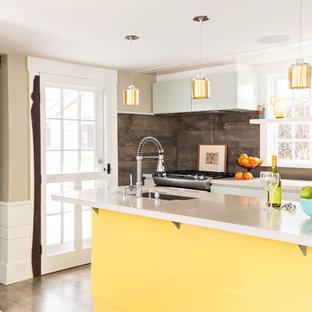 Réalisation d'une cuisine marine avec un évier encastré, un placard à porte plane, des portes de placard blanches, une crédence marron, un électroménager en acier inoxydable, un sol en bois brun et un îlot central.