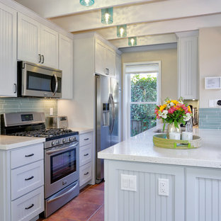 This is an example of a mid-sized beach style galley open plan kitchen in Other with a single-bowl sink, quartz benchtops, blue splashback, glass tile splashback, stainless steel appliances, white cabinets, terra-cotta floors and a peninsula.