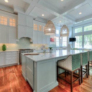 Inredning av ett maritimt vit vitt kök med öppen planlösning, med en undermonterad diskho, skåp i shakerstil, vita skåp, grönt stänkskydd, stänkskydd i glaskakel, rostfria vitvaror, mellanmörkt trägolv, en köksö och brunt golv