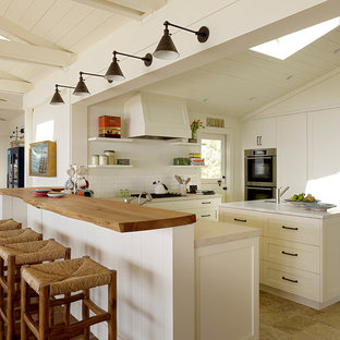 Large beach style u-shaped open plan kitchen in San Francisco with shaker cabinets, white cabinets, white splashback, subway tile splashback, stainless steel appliances, with island, an undermount sink, quartzite benchtops, ceramic floors and beige floor.