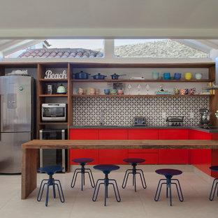 Exemple d'une cuisine bord de mer en L avec un placard à porte plane, des portes de placard rouges, une crédence multicolore, un électroménager en acier inoxydable, une péninsule et un sol beige.