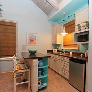 Design ideas for a small beach style single-wall eat-in kitchen in Dallas with a drop-in sink, raised-panel cabinets, white cabinets, laminate benchtops, brown splashback, stainless steel appliances, porcelain floors and with island.