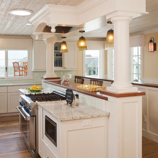 Design ideas for a small beach style kitchen in Los Angeles with recessed-panel cabinets, white cabinets, blue splashback, stainless steel appliances, medium hardwood floors, recycled glass benchtops, glass tile splashback and with island.