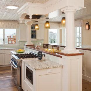 Cette photo montre une petit cuisine bord de mer avec un placard avec porte à panneau encastré, des portes de placard blanches, une crédence bleue, un électroménager en acier inoxydable, un sol en bois brun, un plan de travail en verre recyclé, une crédence en carreau de verre et un îlot central.