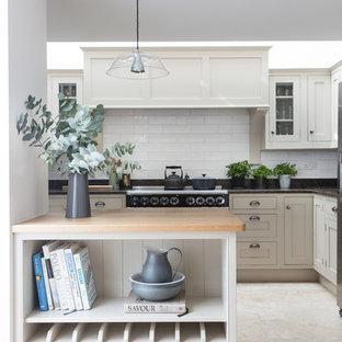 Foto de cocina marinera con armarios estilo shaker, puertas de armario blancas, salpicadero blanco, salpicadero de azulejos tipo metro, suelo de travertino y península