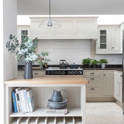 Beach style travertine floor kitchen photo in London with shaker cabinets, white cabinets, white backsplash, subway tile backsplash and a peninsula