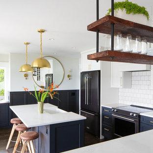 シアトルのエクレクティックスタイルのおしゃれなキッチン (エプロンフロントシンク、シェーカースタイル扉のキャビネット、青いキャビネット、白いキッチンパネル、サブウェイタイルのキッチンパネル、黒い調理設備、濃色無垢フローリング、白いキッチンカウンター) の写真