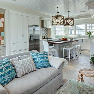 Mid-sized beach style l-shaped open plan kitchen in New York with a farmhouse sink, shaker cabinets, white cabinets, glass benchtops, grey splashback, mosaic tile splashback, stainless steel appliances, ceramic floors and with island.