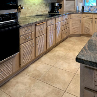 Photo of a mid-sized contemporary u-shaped eat-in kitchen in DC Metro with louvered cabinets, light wood cabinets, granite benchtops, black appliances, ceramic floors, with island, beige floor and multi-coloured benchtop.