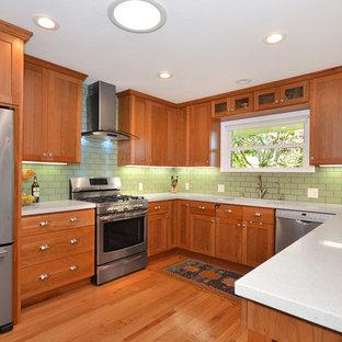 サンフランシスコの中サイズのビーチスタイルのおしゃれなキッチン (クオーツストーンカウンター、シングルシンク、シェーカースタイル扉のキャビネット、中間色木目調キャビネット、緑のキッチンパネル、シルバーの調理設備の、無垢フローリング、アイランドなし、磁器タイルのキッチンパネル) の写真