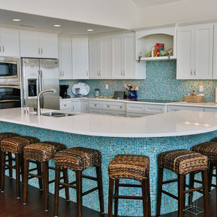 Esempio di un'ampia cucina costiera con lavello a doppia vasca, ante in stile shaker, ante bianche, paraspruzzi blu, paraspruzzi con piastrelle a mosaico, elettrodomestici in acciaio inossidabile, parquet scuro, isola, top in quarzo composito e pavimento marrone