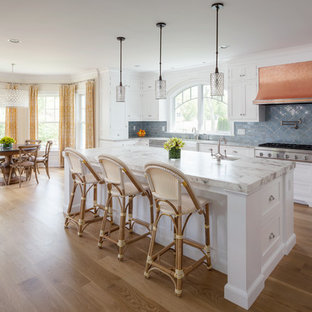 Beach style eat-in kitchen inspiration - Example of a coastal galley medium tone wood floor eat-in kitchen design in Baltimore with a farmhouse sink, white cabinets, marble countertops, blue backsplash, ceramic backsplash, stainless steel appliances, an island and shaker cabinets