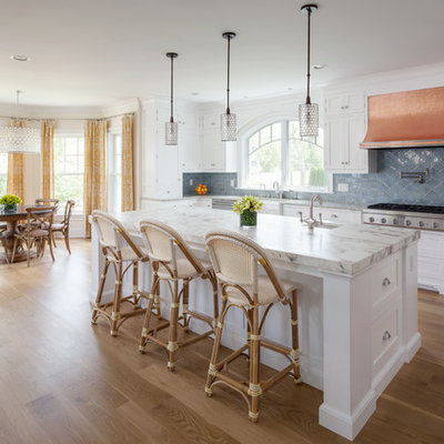 Example of a beach style galley medium tone wood floor eat-in kitchen design in Baltimore with a farmhouse sink, white cabinets, marble countertops, blue backsplash, ceramic backsplash, stainless steel appliances, an island and shaker cabinets