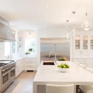 Bild på ett stort maritimt vit vitt kök och matrum, med en undermonterad diskho, luckor med glaspanel, vita skåp, vitt stänkskydd, rostfria vitvaror, ljust trägolv, en köksö och bänkskiva i kvarts
