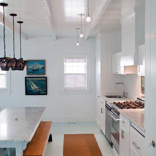 Maritim inredning av ett kök, med rostfria vitvaror och vitt golv