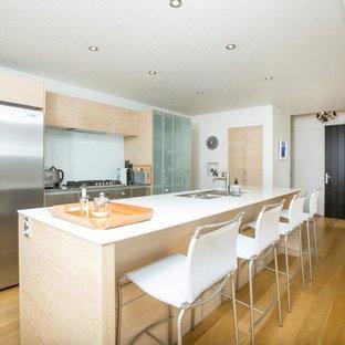 オークランドのビーチスタイルのおしゃれなキッチン (ダブルシンク、ガラス扉のキャビネット、中間色木目調キャビネット、クオーツストーンカウンター、白いキッチンパネル、ガラスタイルのキッチンパネル、シルバーの調理設備の、無垢フローリング) の写真