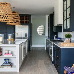 Exemple d'une cuisine bord de mer de taille moyenne avec un évier de ferme, un placard à porte vitrée, des portes de placard bleues, un électroménager en acier inoxydable, un sol en bois clair, un îlot central, un sol gris et un plan de travail gris.