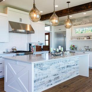 Offene, Mittelgroße Maritime Küche in L-Form mit Unterbauwaschbecken, Schrankfronten im Shaker-Stil, weißen Schränken, Quarzwerkstein-Arbeitsplatte, Küchenrückwand in Weiß, Rückwand aus Keramikfliesen, Küchengeräten aus Edelstahl, braunem Holzboden, Kücheninsel und braunem Boden in Seattle