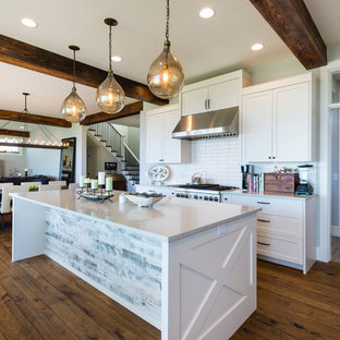 Inspiration for a mid-sized coastal l-shaped medium tone wood floor and brown floor open concept kitchen remodel in Seattle with an undermount sink, shaker cabinets, white cabinets, quartz countertops, white backsplash, ceramic backsplash, stainless steel appliances and an island