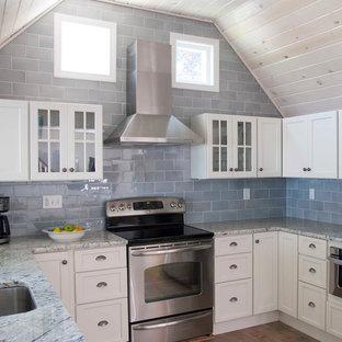 Inredning av ett maritimt kök, med luckor med infälld panel, granitbänkskiva, rostfria vitvaror, vita skåp, blått stänkskydd och stänkskydd i keramik
