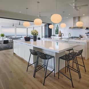 Esempio di una grande cucina design con lavello sottopiano, ante lisce, ante bianche, top in superficie solida, paraspruzzi bianco, paraspruzzi con piastrelle diamantate, elettrodomestici in acciaio inossidabile, parquet chiaro, 2 o più isole e pavimento giallo