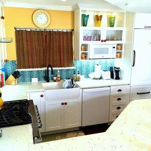 Mittelgroße Maritime Wohnküche ohne Insel in L-Form mit Waschbecken, Schrankfronten im Shaker-Stil, weißen Schränken, Kalkstein-Arbeitsplatte, Küchenrückwand in Blau, Rückwand aus Stäbchenfliesen, weißen Elektrogeräten und dunklem Holzboden in Los Angeles