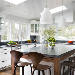 Inspiration for a large transitional eat-in kitchen in New York with glass-front cabinets, white cabinets, limestone benchtops and with island.