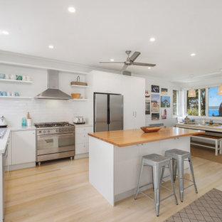 Photo of a beach style l-shaped kitchen in Central Coast with a drop-in sink, flat-panel cabinets, white cabinets, white splashback, subway tile splashback, stainless steel appliances, light hardwood floors, with island, beige floor and white benchtop.