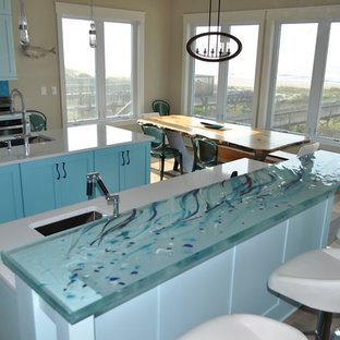 Mid-sized beach style eat-in kitchen ideas - Example of a mid-sized coastal galley light wood floor eat-in kitchen design in Montreal with an undermount sink, shaker cabinets, blue cabinets, glass countertops, blue backsplash, stainless steel appliances, no island and turquoise countertops